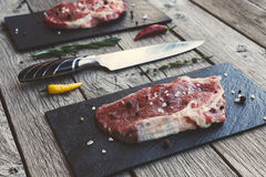 Raw beef steak on dark wooden table background. Fresh juicy meat on black stone cutting desk, knife and lemon slice. Cooking ingredients, butcher`s and grocery Stock Image