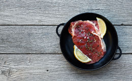 Raw beef steak on dark wooden table background, top view. Raw beef steak in craft paper on dark wooden table background, top view. Fresh juicy meat with herbs Royalty Free Stock Photos