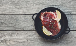 Raw beef steak on dark wooden table background, top view. Raw beef steak in craft paper on dark wooden table background, top view. Fresh juicy meat with herbs Stock Photography