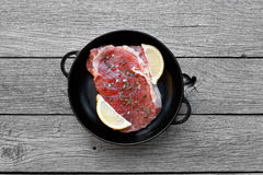 Raw beef steak on dark wooden table background, top view. Raw beef steak in pan on dark wooden table background, top view. Fresh juicy meat with herbs and lemon Stock Photos