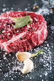 Raw beef steak fillet with ingredients like sea salt, pepper, bay leaves and onion on black board, image for restaurant,. Modern gastronomy Royalty Free Stock Image