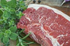 Raw Beef Steak with Fresh Herbs on Board. Raw beef steak with fresh herbs, on wooden board Royalty Free Stock Image