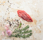 Raw beef steak. Raw fresh meat Ribeye steak entrecote and seasonings with pepper and salt on a marble countertop. Young garlic, cherry tomatoes and rosemary. Top Stock Image
