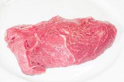 Raw beef steak. Fresh raw beef steak on a white plate Royalty Free Stock Image