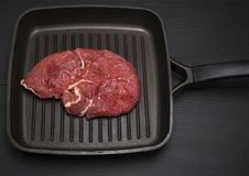Raw beef steak in a frying pan. For cooking on a black wooden table Royalty Free Stock Image