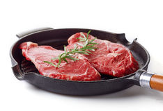 Raw beef steak on frying pan ready to cook, isolated on white Stock Image
