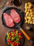 Raw beef steak on grill pan from above. Raw beef steak on grill pan, potatoes, spices and tomatoes, top view, on wooden table royalty free stock photo