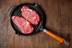 Raw beef steak on grill pan from above. Raw beef steak on grill pan, on wooden table, top view stock photography