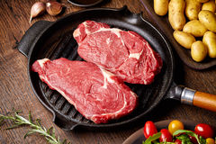 Raw beef steak on grill pan royalty free stock photo