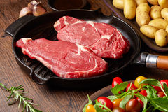 Raw beef steak on grill pan. Potatoes, spices and tomatoes on wooden table Stock Image