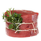 Raw Beef Steak with Herbs Isolated. Raw beef steak tied with fresh herbs, isolated on white Royalty Free Stock Photography