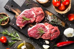 Raw beef steak with herbs. Raw meat. Raw beef steak on a cutting board with rosemary and spices. Top view Stock Photos