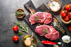 Raw beef steak with herbs. Raw meat. Raw beef steak on a cutting board with rosemary and spices. Top view copy space Royalty Free Stock Photo
