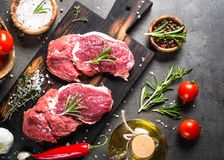 Raw beef steak with herbs. Raw meat. Raw beef steak on a cutting board with rosemary and spices. Top view copy space Royalty Free Stock Photos