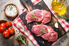 Raw beef steak with herbs. Top view. Beef steak on a cutting board with rosemary and spices. Fresh meat. Top view Stock Images