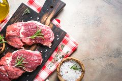 Raw beef steak with herbs. Top view. Fresh meat. Raw beef steak on a cutting board with rosemary and spices. Top view copy space Stock Photography
