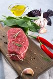 Raw beef steak with ingredients for cooking on cutting board . On a gray concrete background Royalty Free Stock Image