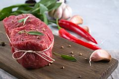 Raw beef steak with ingredients for cooking on cutting board . On a gray concrete background Royalty Free Stock Images
