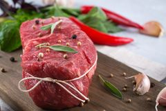 Raw beef steak with ingredients for cooking on cutting board . On a gray concrete background Royalty Free Stock Photography