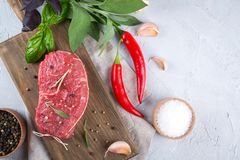 Raw beef steak with ingredients for cooking on cutting board . Top view with copy space Stock Image