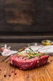 Raw beef steak with ingredients for cooking on rustic kitcen table over dark woden background. Raw beef steak with ingredients for cooking rustic kitcen table stock images