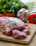 Raw beef steak with ingredients vegetables. On a wooden board Royalty Free Stock Images