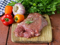 Raw beef steak with ingredients vegetables. On a wooden board Royalty Free Stock Photo