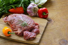Raw beef steak with ingredients vegetables. On a wooden board Stock Photos