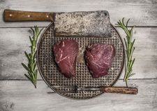 Raw beef steak on an iron pan with rosemary, meat cleaver and fork on bright, rustic wood background top view close up. Raw beef steak on iron pan with rosemary Royalty Free Stock Images