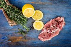 Raw beef steak with lemon and rosemary. On a blue  wooden table Stock Photo