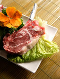 Raw Beef Steak on Lettuce. Raw beef steak on plate with iceberg lettuce and an orange pansy Stock Photos