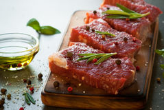 Raw beef steak. Raw meat. Raw beef steak on a cutting board with rosemary and spices Stock Photo