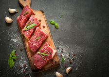 Raw beef steak. Raw meat. Raw beef steak on a cutting board with rosemary and spices royalty free stock photo