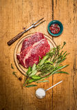 Raw beef steak with meat fork, fresh herbs an spoon of salt on rustic  wooden background Stock Images