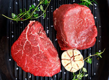 Raw Beef steak Mignon. thyme, garlic, salt on grilled pan. Stock Images