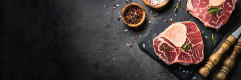 Raw beef steak osso bucco on black. Marble meat. Raw beef steak osso bucco on black stone slate background. Marble meat. Top view with copy space. Long banner Royalty Free Stock Images