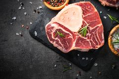 Raw beef steak osso bucco on black. Marble meat. Raw beef steak osso bucco on black stone slate background. Marble meat. Top view, close up Stock Images