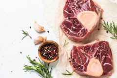 Raw beef steak osso bucco. Marble meat. Raw beef steak osso bucco and ingredients for cooking. Marble meat. Top view with copy space on white table Royalty Free Stock Photography