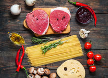 Raw beef steak with pasta, tomatoes, mushrooms and cheese on dark table background, top view food concept Royalty Free Stock Photo