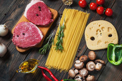 Raw beef steak with pasta, tomatoes, mushrooms and cheese on dark table background, top view food concept Royalty Free Stock Photos