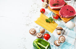 Raw beef steak with pasta, tomatoes, mushrooms and cheese on white table background,copyspace Stock Photos