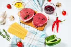 Raw beef steak with pasta, tomatoes, mushrooms and cheese on white table background Royalty Free Stock Photos