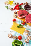 Raw beef steak with pasta, tomatoes, mushrooms and cheese on white table background Stock Image
