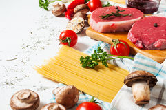 Raw beef steak with pasta, tomatoes, mushrooms and cheese on white table background Stock Photography