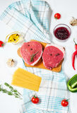 Raw beef steak with pasta, tomatoes, mushrooms and cheese on white table background, top view Stock Photography