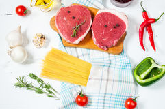 Raw beef steak with pasta, tomatoes, mushrooms and cheese on white table background, top view Royalty Free Stock Photography