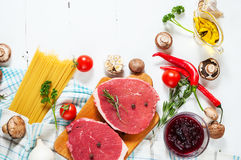Raw beef steak with pasta, tomatoes, mushrooms and cheese on white table background, top view Stock Photo