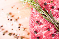 Raw beef steak with pepper and rosemary on a wooden table Royalty Free Stock Photo