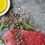 Raw Beef Steak with Peppercorns Sea Salt Olive Oil and Rosemary. Raw beef steak with peppercorns, sea salt, olive oil and rosemary, over dark slate.  Overhead Royalty Free Stock Image