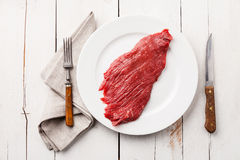 Raw beef steak on plate. Prime cut of beef steak on plate on white wooden background Royalty Free Stock Photos